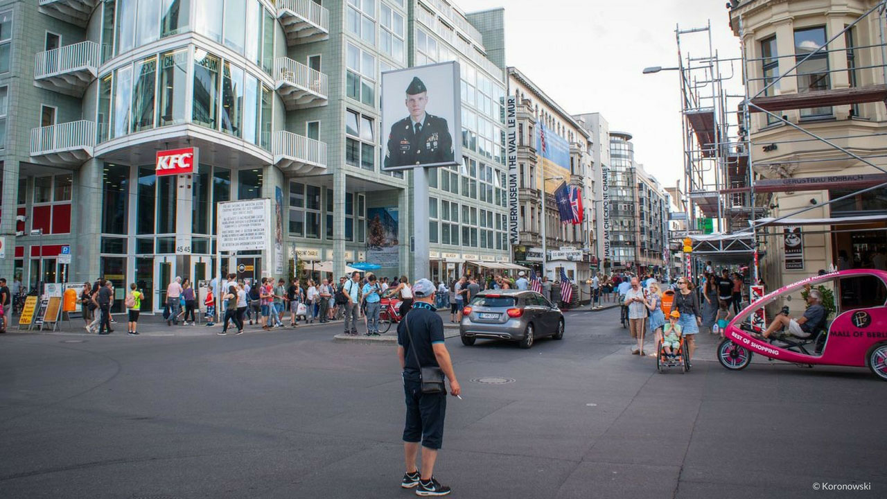 The Checkpoint Charlie in Berlin. The big glowing image shows an American or a Soviet soldier, depending on which side you are standing.