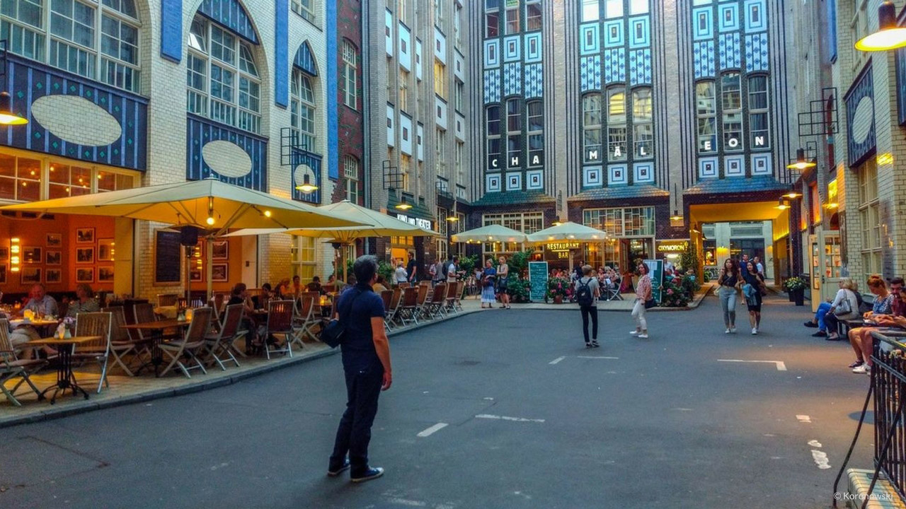 In the Summer bustle, people are sitting outside in front of the restaurants around the Hackesche Höfe in Berlin.